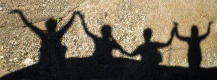 Schatten von glücklichen Menschen mit den Armen hoben auf Felsen an Lizenzfreie Stockbilder