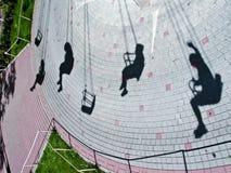 Schatten von Leuten auf einem Karussell Lizenzfreie Stockfotografie