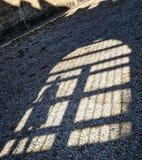 Schatten von Mädchen im Bogen des Bogens auf den Kopfsteinen der alten Stadt Stockbilder
