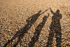 Schatten von 3 Menschen auf Pebble Beach Lizenzfreies Stockfoto