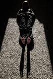 Schatten von Person Lying auf Floow mit Sonnenlichtbeinfüßen Lizenzfreies Stockfoto