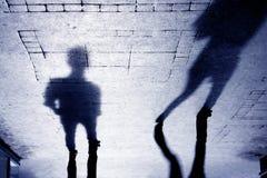Schatten von Zweipersonen auf patterened Bürgersteig lizenzfreie stockfotos