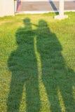 Schatten von Zwillingsleute Händchenhalten im Garten stockfotos