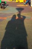 Schatten von Zwillingsleute Händchenhalten im Garten lizenzfreie stockfotografie