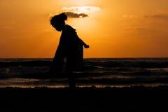 Schattenbild auf einem Strand bei Sonnenuntergang Stockbilder