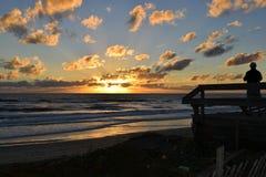 Schattenbild auf Strandplattform bei Sonnenuntergang Lizenzfreie Stockbilder