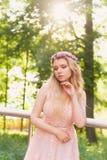 Schattenbild, das in die untergehende Sonne im schönen Holz der Braut im Pfirsichkleid mit Spitze wirbelt Blondine mit a Lizenzfreie Stockfotos