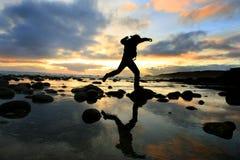 Schattenbild, das am Sonnenuntergang springt Stockbilder