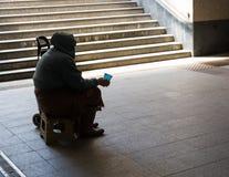 Schattenbild der älteren Frau bitten um Almosen in der Unterführung Co Stockfotografie
