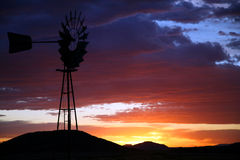Schattenbild der Bauernhof-Windmühle bei Sonnenuntergang Stockbilder