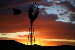 Schattenbild der Bauernhof-Windmühle bei Sonnenuntergang Lizenzfreies Stockfoto