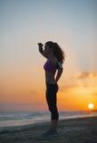 Schattenbild der Eignungsfrau untersuchend Abstand auf Strand Lizenzfreie Stockfotografie