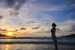 Schattenbild der einzelnen jungen Frau auf Strand wenn Sonnenuntergang Stockfoto