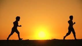Schattenbild der fünf Kinderfamilie, die bei Sonnenuntergang runniing ist stock video footage