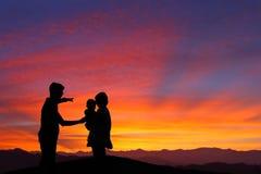 Schattenbild der Familie den Sonnenaufgang überwachend Stockfotografie
