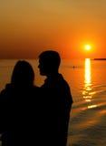 Schattenbild der Familie im Sonnenuntergang Stockfotografie