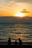 Schattenbild der Familie spielend auf dem Strand bei Sonnenuntergang stockfoto