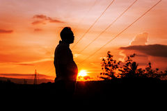 Schattenbild der fetten Stellung des Mannes bei Sonnenuntergang Stockbilder