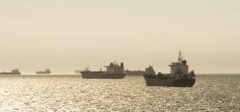 Schattenbild der Frachtschiffe über dem Sonnenaufgang Lizenzfreies Stockfoto