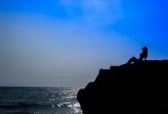 Schattenbild der Frau auf dem Seestrand bei dem Sonnenuntergang, der auf dem Stein sitzt stockfotografie