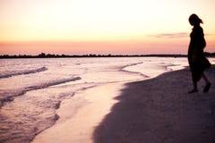 Schattenbild der Frau auf Küste am Sonnenuntergang Stockbilder