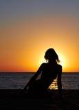 Schattenbild der Frau auf Seeküste am Sonnenaufgang Stockfoto