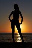 Schattenbild der Frau auf Seeküste am Sonnenaufgang Lizenzfreies Stockbild