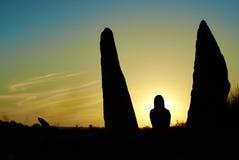 Schattenbild der Frau an den hellen Strahlen des Sonnenuntergangs stockfotografie