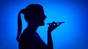 Schattenbild der Frau, die Mobiltelefon auf blauem Hintergrund verwendet Weibliches ` s Gesicht im Profil, das mit Freund spricht stock video footage