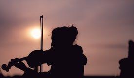 Schattenbild der Frau die Violine während des Sonnenuntergangs gegen das sonnen- eingelassene Prag spielend lizenzfreie stockbilder