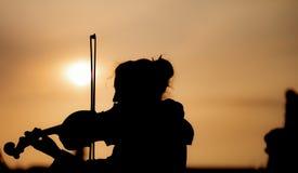 Schattenbild der Frau die Violine während des Sonnenuntergangs gegen das sonnen- eingelassene Prag spielend stockfoto