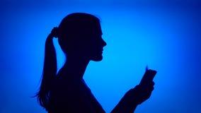 Schattenbild der Frau Geld auf blauem Hintergrund zählend Weibliches ` s Gesicht im Profil mit Bündel Rechnungen stock video