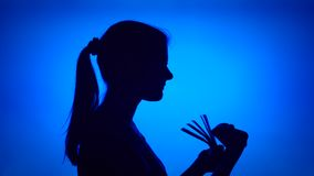Schattenbild der Frau Geld auf blauem Hintergrund zählend Weibliches ` s Gesicht im Profil mit Bündel Rechnungen stock footage