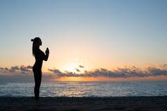 Schattenbild der Frau Gruß zur Sonne auf dem Strand bei Sonnenaufgang, Morgenyoga tuend lizenzfreies stockfoto