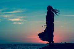 Schattenbild der Frau im langen Kleid, das auf der Küste nach Sonnenuntergang steht nave Lizenzfreies Stockbild