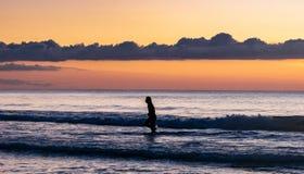 Schattenbild der Frau laufend in den Ozean während des Sonnenuntergangs in Borneo-Insel, Malaysia lizenzfreie stockfotos