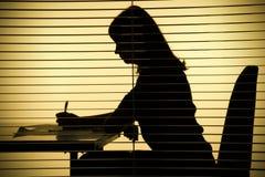 Schattenbild der Frau mit Papieren (Ansicht durch die Vorhänge) Lizenzfreies Stockfoto