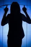 Schattenbild der Frau schauend durch die Vorhänge Lizenzfreies Stockbild