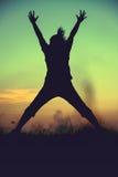 Schattenbild der Frau springend gegen Sonnenuntergang Genießen des jungen Mädchens Lizenzfreies Stockfoto