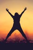 Schattenbild der Frau springend gegen Sonnenuntergang Genießen des jungen Mädchens Stockfotografie