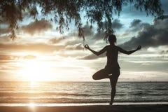 Schattenbild der Frau stehend an der Yogahaltung auf dem Strand während des Sonnenuntergangs Stockbilder