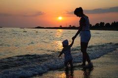 Schattenbild der Frau und des Schätzchens auf Sonnenuntergang Stockbild