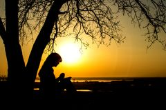 Schattenbild der Frau zum Gott im Natur witth die Bibel betend am Sonnenuntergang, am Konzept der Religion und an der Geistigkeit lizenzfreie stockfotografie