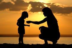 Schattenbild der Frauen, zum des Kindes des Sandes in der Hand zu gießen Stockfotografie