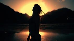 Schattenbild der Frauenstellung bei Sonnenuntergang silhouettiert Nass schwinghaar stock video
