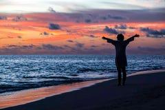 Schattenbild der freien Frau die Freiheit genießend, die am Strand glücklich sich fühlt Stockfoto