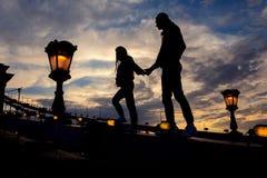 Schattenbild der gehenden Paare durch die Hand entlang der Hängebrücke voll von BlitzStraßenlaternen in Budapest, Ungarn Stockfoto