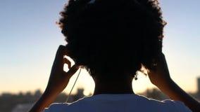 Schattenbild der gelockten Frau setzend auf Kopfhörer, magische Stunde genießend stock footage