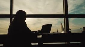 Schattenbild der Geschäftsfrau in der Klage, arbeitend mit Laptop im Flughafenabfertigungsgebäude stock video