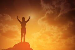 Schattenbild der gewinnenden Erfolgsfrau bei dem Sonnenuntergang oder Sonnenaufgang, die oben ihre Hand in der Feier stehen und a stockbilder